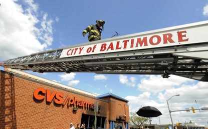 Baltimore, MD--4/28/15- Fire trucks returned to the CVS on North Ave. to check out a possible fire in the CVS that was looted and burned the day before as part of the protests over the death of Freddie Gray after being injured in police custody.(Lloyd Fox/Baltimore Sun)