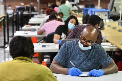 Francis Vincent, facing camera, records votes read to him by his partner as canvassers recreate ballots that can be read by the scanner. Vote canvassing for the primary continues at the Baltimore City Board of Elections warehouse. June 8, 2020