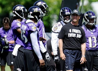 Ravens head coach John Harbaugh works with players during a June 13 minicamp at the Ravens' Owings Mills training facility.