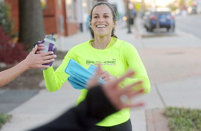 Betty Shock of Fallston gets high fives from fellow runners as she finishes a community run in honor of Boston Marathon bombing victims, organized by Charm City Run, in Bel Air, Md., on Monday April 22, 2013.