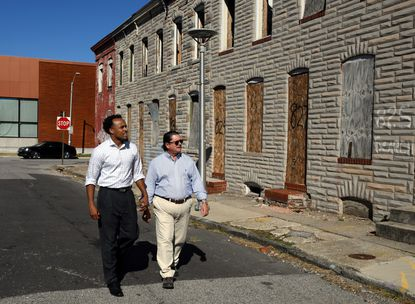 Khalil Uqdah, left, and Larry Rosenberg of Cross Street Partners walk along the 800 block of Madeira St. in East Baltimore, where they are building a new development called Henderson Crossing.
