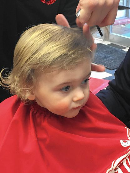 Not too much squirming is observed as Evan Lloyd receives his first haircut at Old Line Barbers in Bel Air.