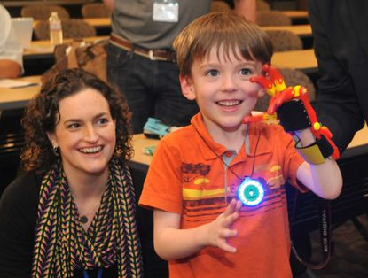 """Griffin Matuszek, 5 1/2, tries out his new 3-D hand, as Quinn Cassidy, his mother, left, and others watch at a symposium, """"Prosthetists Meet Printer: Mainstreaming Open Source 3-D Printed Prosthetics for Underserved Populations,"""" sponsored by Hopkins Medicine."""
