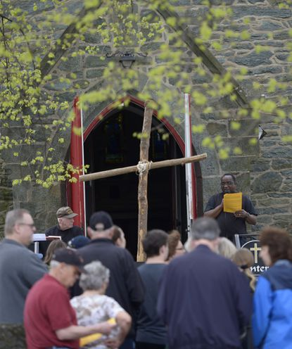 The Rev. Samuel Nsengiyumva addresses participants in front of Church of the Ascension at the beginning of the 2019 Good Friday Community Cross Walk, April 19. Nsengiyumva said he discovered while checking the church's voicemailbox a message containing the sound of gunfire on Saturday. The church canceled Sunday services and children's activities for Monday and Tuesday. Westminster police are investigating.