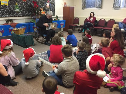 Saint Joseph Catholic Community will host its annual Breakfast with Saint Nick on Dec. 7. Father Neville, pictured, reads a story to children at a previous year's event.