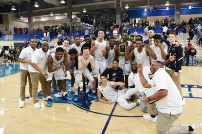 John Carroll boys basketball team poses for a picture with the championship plaque after beating Boys' Latin, 58-50, in overtime for the MIAA A Conference on Sunday at APGFCU Arena in Bel Air.