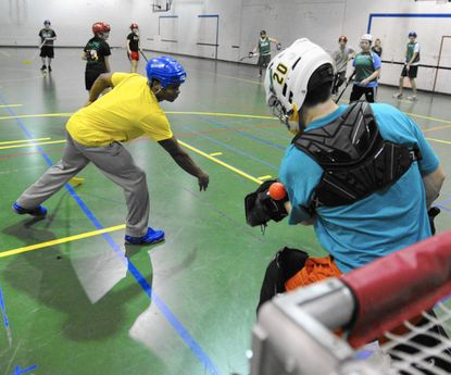 The ball deflects off of goalie Peter Comitale's arm during floor hockey jan term class at McDaniel College on Wednesday.