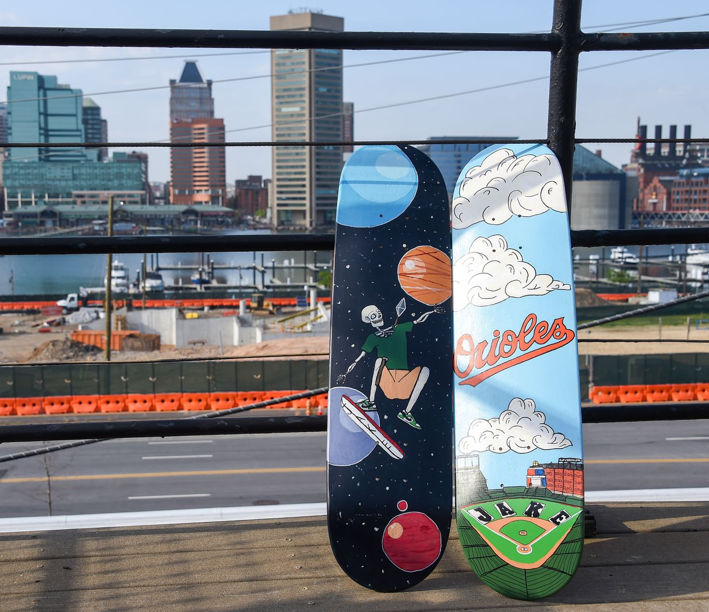 """""""Two Heads are Better Than One"""" and """"A Perfect Day at the Yard"""" by Reid Glaros painted on skateboards sit on the deck of Cindy Conklin on Wednesday, April 7, 2021; the boards will be auctioned off to help fund the completion of Jake's Skate Park at Rash Field, which is seen in the background."""