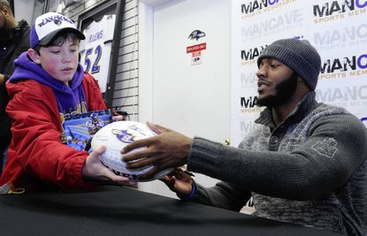 Ravens running back Bernard Pierce autographs a football for Mike McGeeney, 13, of West River, at Man Cave Sports in Glen Burnie.