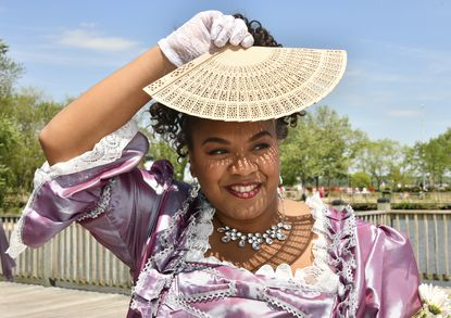 """Crystal Nelson of Washington, D.C., uses her fan for shade at the Bridgerton inspired tea at the Havre de Grace promenade. She and friends also learned other fan techniques at a session called """"Fan Flirting,"""" one of the Regency-era activities offered at the event organized by the Havre de Grace Independence Commission to help fund the 2021 July 4th parade and concert."""