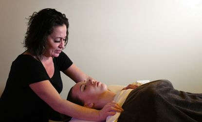 Shay Howard, a massage therapist with About Faces Day Spa, performs a massage on Amber Blevins of Shadyside. She is using a CBD oil product during the massage.