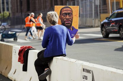 A woman holds a George Floyd picture while seated on a concrete barrier near the Hennepin County Government Center Monday, April 5, 2021, in Minneapolis where the second week of testimony in the trial of former Minneapolis police officer Derek Chauvin continues. Chauvin is charged with murder in the death of George Floyd during an arrest last May in Minneapolis. (AP Photo/Jim Mone)