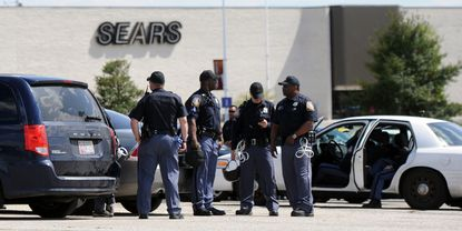 Police assemble in the parking lot at the Security Square Mall, which was closed Tuesday amid reports of possible violence following Monday's riots in the city.