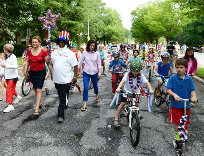 Baltimore City Council President Jack Young, left in Uncle Sam outfit, leads the Roland Park Fourth of July parade down Roland Avenue.