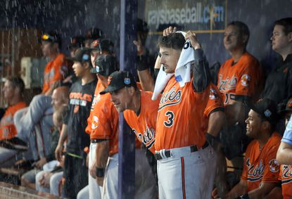 Baltimore Orioles second baseman Ryan Flaherty (3) uses a towel to cover up as he stands with the rest of the team beneath the dugout sheltering from a heaven rain in the first inning of a spring training baseball game against he Tampa Bay Rays on Saturday, March 19, 2016, in Port Charlotte, Fla.Flaherty was optioned to the minors on April 25.