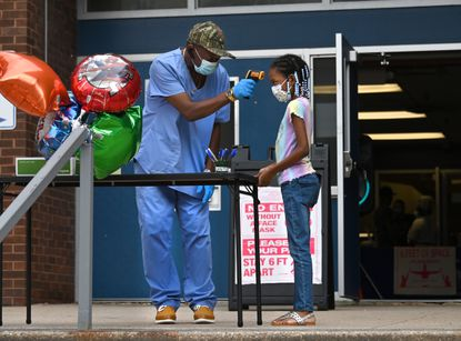 Keith Boyd a former special education teacher who is volunteering at Bernard Harris Elementary School to help with summer school, takes the temperature of Kennedy Harris a second grader before she can enter the school. The students also have to answer several questions about their health before entering each day.