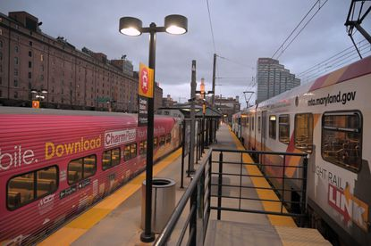 Investing more in services like the MARC train, left, and light rail, right, at Camden Station at Camden Yards might create jobs, reduce crime and lessen the need to hire more city police officers.