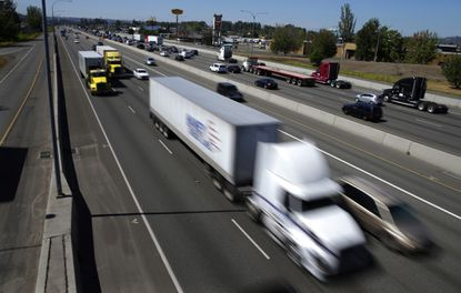 In this Wednesday, Aug. 24, 2016, photo, truck and automobile traffic mix on Interstate 5, headed north through Fife, Wash., near the Port of Tacoma. The federal government wants to limit how fast trucks, buses and other large vehicles can drive on the nation's highways. A new regulation posted Friday, Aug. 26, would impose the nationwide limit by electronically capping speeds with a device on newly-made U.S. vehicles that weigh more than 26,000 pounds.