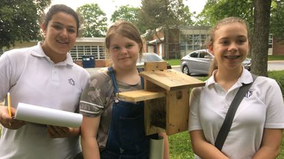 From left, Christina Sousou, Katie Doyle and Audrey Hoffman of Girl Scout Cadette Troop 3948 display a nesting box that was part of their revitalization of the Bluebird Trail at Pot Spring Elementary School. The girls were honored with a Silver Award.