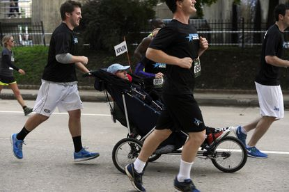 """In wheelchair, Kevin Dilegge, 25, of Baltimore, supported by Athletes Serving Athletes """"Wingmen,"""" participates in the 2014 Baltimore Marathon."""