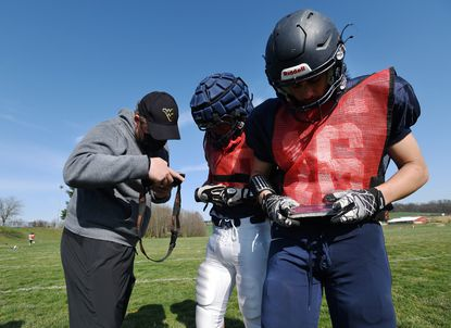 Francis Scott Key defensive line coach Everett Polzin helps Jacob Dell and Noah Geiman, right, as they set up their Go Rout units during a football practice in Uniontown on April 5, 2021. The Go Rout system allows plays in practice to be called using an app so players get the plays without huddling up for a longer period of time.