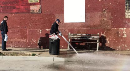 Crew members of the Baltimore Fire Department spray a water hose over blood on a sidewalk after a man was shot and killed in the 1300 block of West Franklin Street on Friday, Feb. 7, 2020.