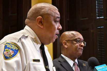 """Police Commissioner Michael Harrison, left, with Mayor Bernard C. """"Jack"""" Young, said they would be making changes to police and city services in order to enforce Gov. Larry Hogan's order that nonessential businesses close to slow the spread of coronavirus."""