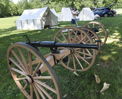 """Maj. Gen. John C. Houck, who re-enacts with a group portraying Company A, 37th Regiment North Carolina Volunteer Troops sets up his tent in front of a Williams breech loading gun and a six-pound mountain howitzer at Union Mills Homestead. Union Mills Homestead will host a Civil War Living History and Encampment """"Citizen Meets Soldier"""" program Saturday and Sunday July 17 and 18. Living history re-enactors will be camped out on the grounds of the homestead and will have exhibits and demonstrations set up each day."""