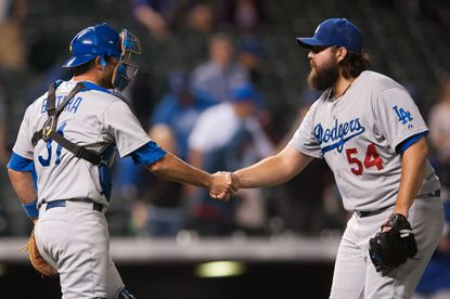 Drew Butera (31) and Chris Perez (54) of the Los Angeles Dodgers celebrate an 11-3 win over the Colorado Rockies at Coors Field on Sept. 15, 2014 in Denver.