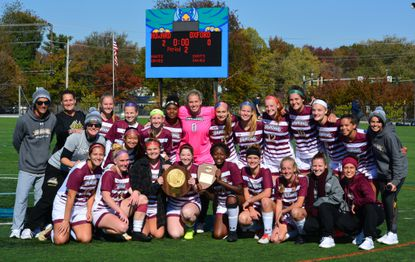 The Howard Community College women's soccer team poses with the regional championship trophy after defeating Oxford 2-0.