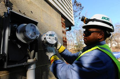 Rudolph Johnson III, a BGE meter crew leader, removes a BGE legacy meter and installs a smart meter on a home on Hoot Owl Road.