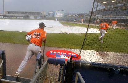 Orioles' Miguel Jabalera (89) sprints out of the dugout following staff and players to the clubhouse in thepouring rain during a spring training game, Saturday, March 19, 2016, in Port Charlotte, Fla. The Orioles game against the Tampa Bay Rays was canceled due to heavy rain in the region.