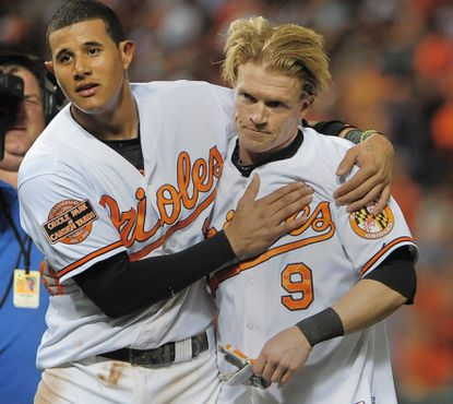 Manny Machado and Nate McLouth, the heroes of Wednesday night' win, walk off the field arm in arm.