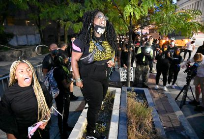 Destini Philpot stands on a concrete planter, rallying supporters with help from fellow Baltimore resident Aniy'a Taylor, left, during a protest for Breonna Taylor outside Baltimore Police Department headquarters on Thursday, Sept. 24.