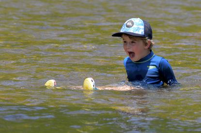 Avoiding the weekend throng, Owen Macey, 6 1/2, of Linthicum reacts to the water temperature at Patapsco State Park's swinging bridge, as the metropolitan area experiences summertime temperatures Wed., April 28, 2021. (Karl Merton Ferron/Baltimore Sun Staff)