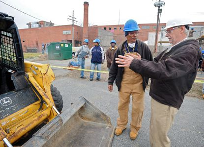 Baltimore would require collective bargaining agreements for major city projects under a proposal introduced Monday before the City Council. In this Feb. 15, 2019, file photo, senior construction instructor Larry Neighoff of the Baltimore Washington Laborer Training Center, gives direction to Michael Mitchell, center, on how to operate a skid steer loader.