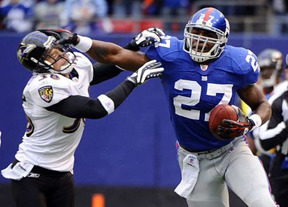 New York Giants running back Brandon Jacobs (right) stiff-arms Ravens safety Jim Leonhard during a 36-yard run in the first quarter.