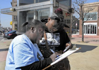 At the Penn North intersection, Communities United set up a table where ex-offenders and others could register to vote. Trina Ashley, left, helps Da'Shai Williams, -- who says she is a former felon -- fill out a voter registration form. Proposed legislation would require registration forms be given to inmates as they leave prison.