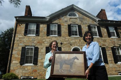 Carol Allen (left), director of the of Harford Community College library, and Maryanna Skowronski, director of the Historical Society of Harford County, with a photogravure portrait of racehorse Durbar at the Hayes-Heighe House at HCC.