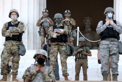 Members of the D.C. National Guard stand on the steps of the Lincoln Memorial monitoring demonstrators during a peaceful protest against police brutality and the death of George Floyd. President Trump tweeted Sunday that he had ordered the National Guard to withdraw from Washington D.C.