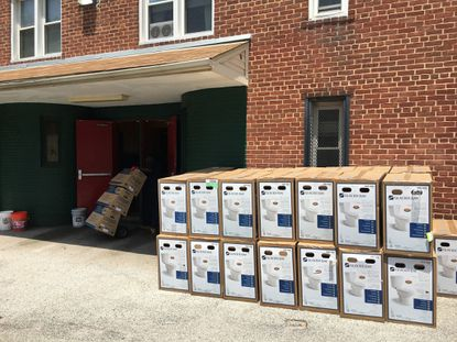 Workers deliver hundreds of replacement toilets to the Poe Homes public-housing complex, which recently endured more than a week of water problems.