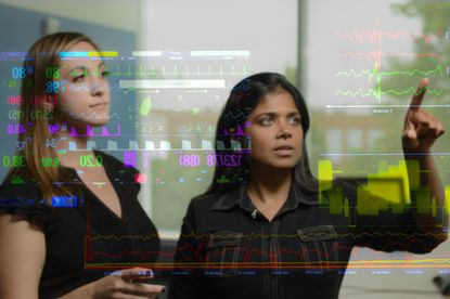 Suchi Saria, right, an assistant professor of computer science and health policy at Johns Hopkins' Whiting School of Engineering  and Katharine Henry, a Ph.D student in Saria's lab analyze information on critically ill patients.