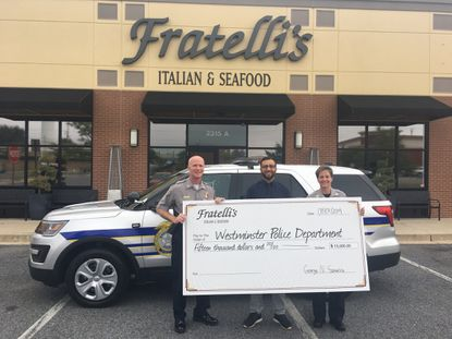 Fratelli's Italian and Seafood presented a supersized $15,000 check to the Westminster Police Department Friday. Chief Thomas Ledwell, owner George Sakellis and Capt. Nikki Heuer (left to right).
