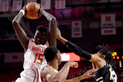 Chol Marial of Maryland rebounds in front of Mikail Simmons of Bryant during the first half at Xfinity Center on December 29, 2019 in College Park.