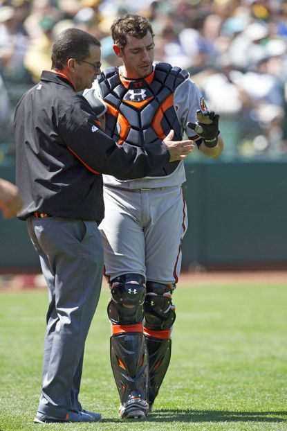 Taylor Teagarden is attended to by Orioles trainer Richie Bancells after dislocating his thumb Saturday in Oakland.