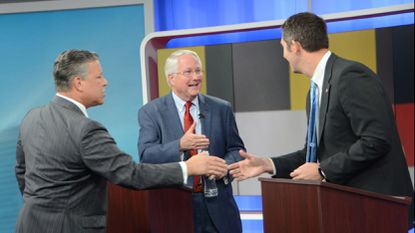 Sinclair Broadcasting's Mark Hyman, left, greets Baltimore County executive candidates Al Redmer Jr., center, and Johnny Olszewski Jr. after recording a debate at WBFF studios in Baltimore on Wednesday afternoon. Hyman moderated the debate.