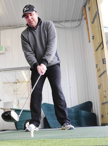 Matthew Ferguson, pro at Churchville Golf Center, gets a few practice swings in from the indoor driving area at the golf center.