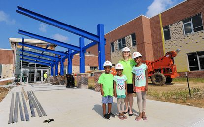 Lyons Mill Elementary School Principal Maralee Clark, third from left, stands with, from left, first-grader Nate Smith, 6, second-grader Bailey Tutman, 6, and fifth-grader Blake Tutman, 9, all of Owings Mills, outside the new Owings Mills school, which was still under construction on July 28.