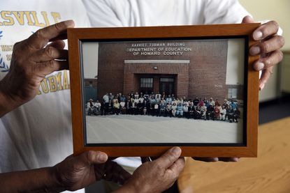 Graduates of Harriet Tubman High School gather at the former building, which is now a facility the Howard County Board of Education. Here, they hold a photo taken in 2004 at the unveiling of the Harriet Tubman sign on the building.