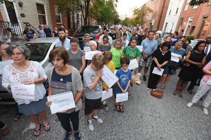 Residents gather at the 1200 block of Riverside Avenue to pray for the city's homicide victims including Timothy Moriconi, 25, who was killed on the block last year. On Monday a Baltimore jury convicted his killer, De'Andre Sleet.